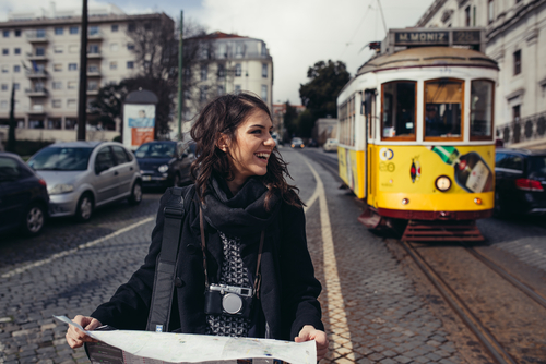 Female studying abroad holding a map standing next to a tram