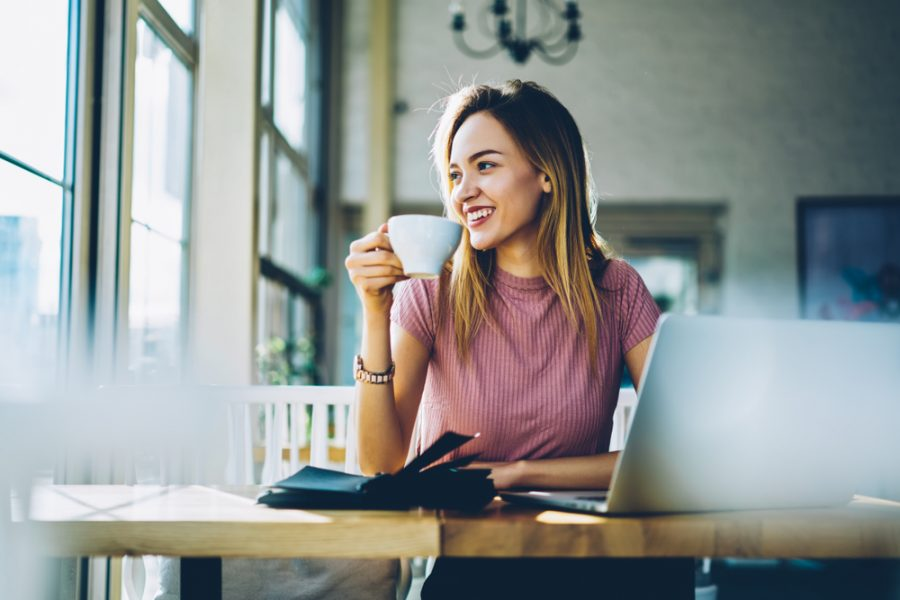 Female student sitting at a table, sipping coffee, and using her laptop at one of the best coffee shops to study at in Austin