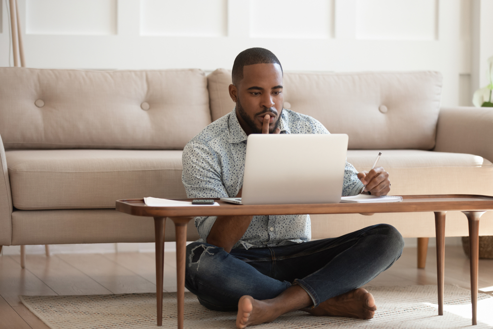 A young man sitting on the floor in his living room and doing research on his computer.