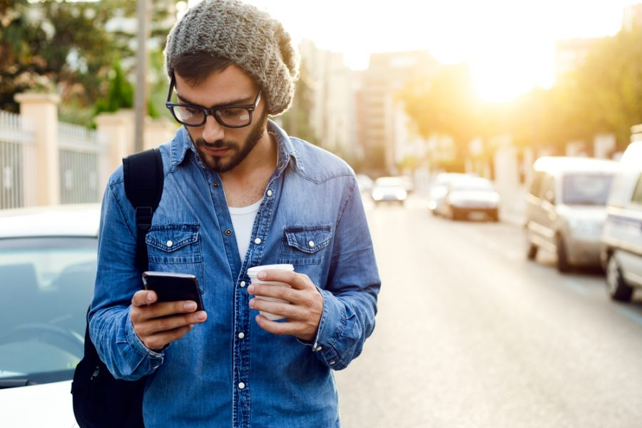 A male student holding a cup of coffee and finding last-minute student accommodation on his phone.