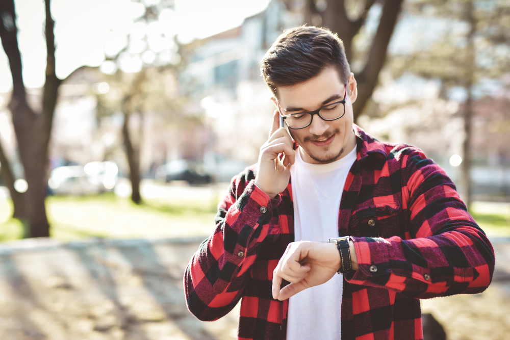 A young male looking standing outside on his phone while simultaneously looking at his watch.