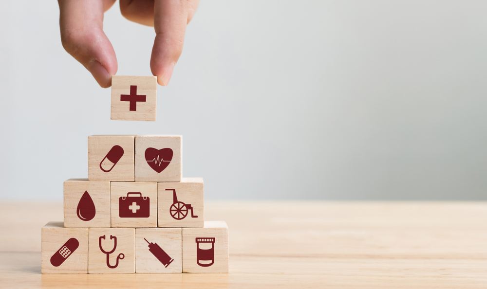 Person stacking wooden building blocks with various healthcare icons on them