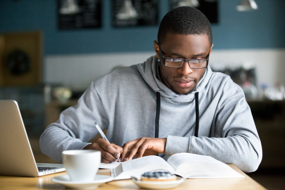 Young male student with glasses sitting at a café table with his laptop and writing in a notebook