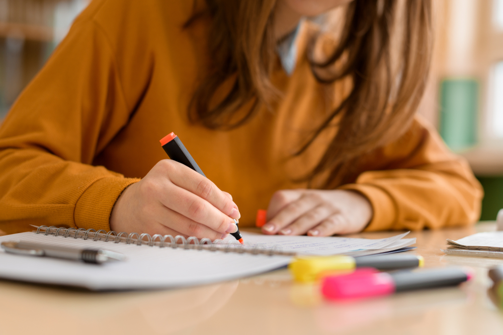 A young, brunette student practicing a student hack and color-coding her class notes with an orange highlighter.