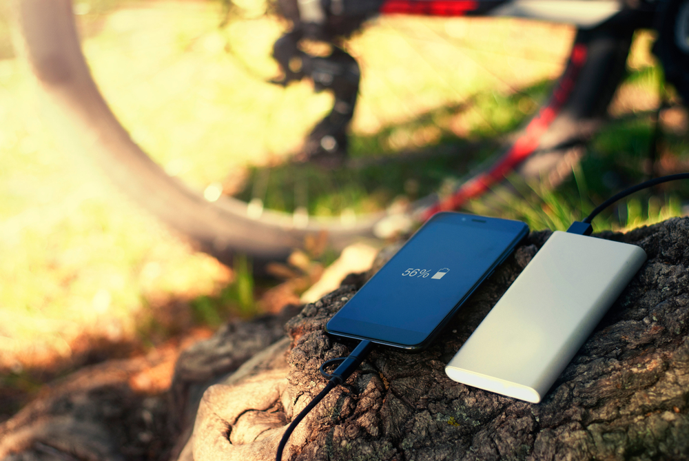 A cell phone and portable cell phone charger on a log in a park with a red bicycle in the background