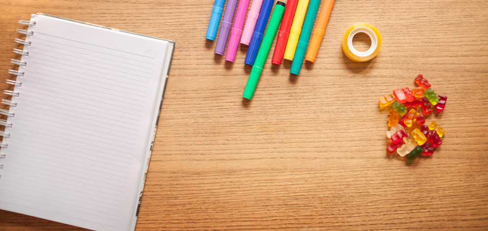 A desk with colorful gummy bears, tape, multicolored pens, and a spiral notebook