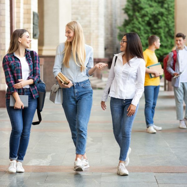 Group of college women walking on campus and discussing how to survive Australia as students.