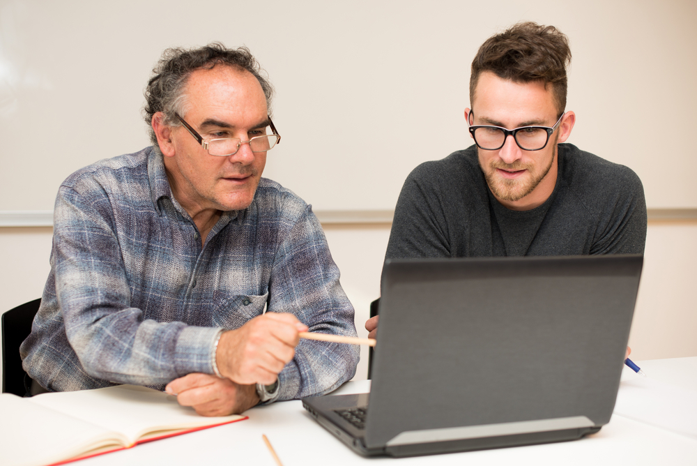 A young male student with glasses sitting at his laptop with his mentor who is pointing to something on the computer screen