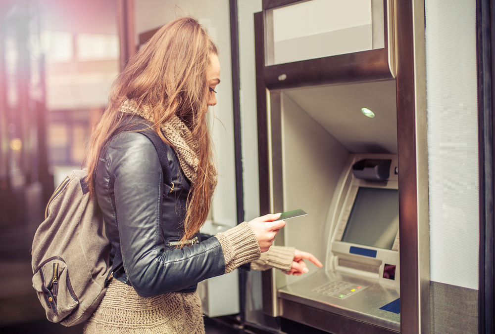 Young woman with a backpack on withdrawing money from an ATM