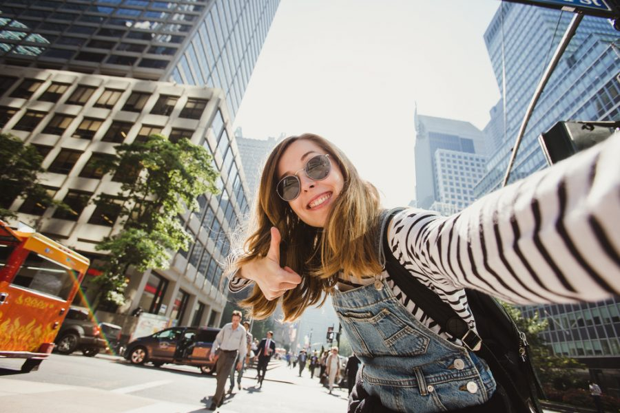 Young female student taking a thumbs-up selfie against the backdrop of one of the best cities for college students