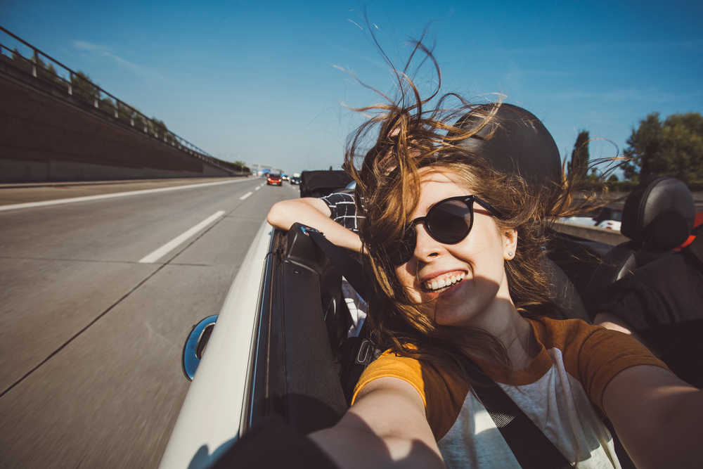 Young woman sitting in the passenger seat of a convertible and taking a selfie