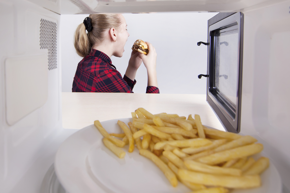 A young blonde student with a ponytail heating a burger and fries in the microwave