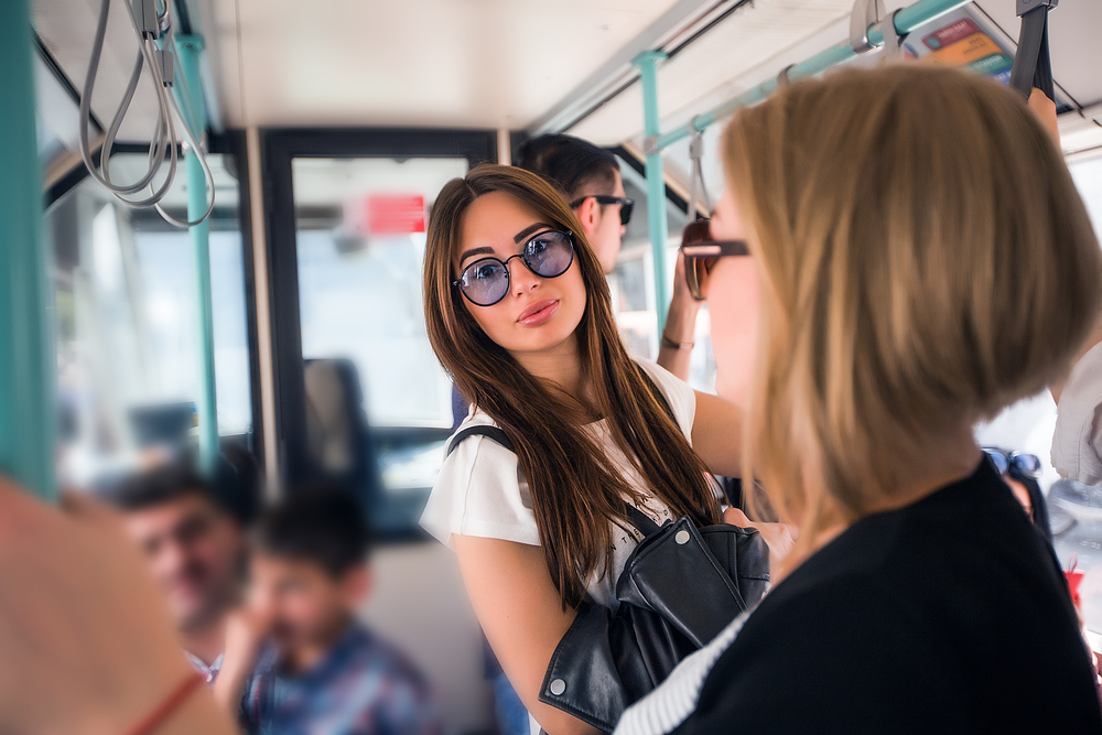 Young brunette woman standing in the aisle of the public bus